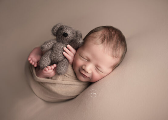 troy michigan newborn photographer melissa anne photography wrapped baby with bear smiling